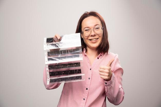 Giovane donna che mostra un pollice in su e che tiene un nastro fotografico su un bianco. foto di alta qualità