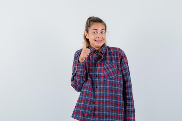 Молодая женщина показывает палец вверх в клетчатой рубашке и выглядит довольно