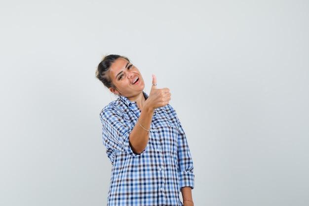 市松模様のシャツに親指を表示し、満足そうに見える若い女性。