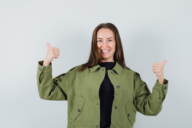 녹색 재킷에 엄지 손가락을 표시 하 고 긍정적 인 찾고 젊은 여자. 전면보기.