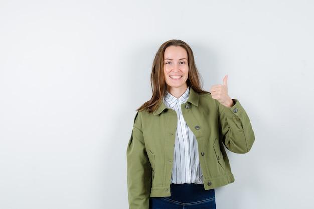 シャツ、ジャケットで親指を表示し、幸せそうに見える若い女性、正面図。