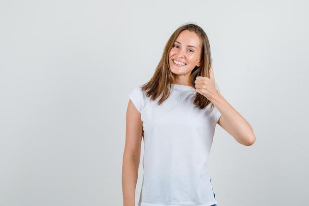 白いtシャツに親指を立てて幸せそうに見える若い女性。正面図。