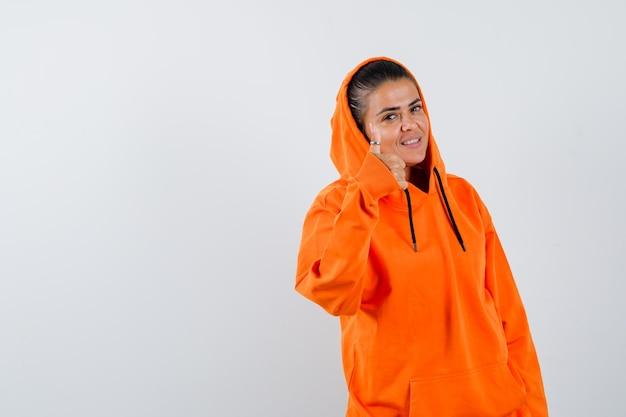 Giovane donna che mostra pollice in su in felpa con cappuccio arancione e sembra bellissima