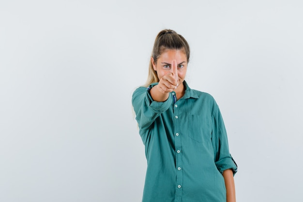 파란색 셔츠에 카메라까지 엄지 손가락을 보여주는 젊은 여자가 기쁘게 찾고