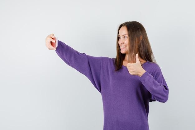 Молодая женщина показывает палец вверх, принимая селфи в фиолетовой рубашке и выглядит счастливым. передний план.