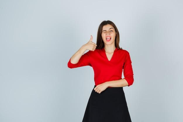 親指を立てて、まばたき、赤いブラウスで口を開いたままにしておく若い女性