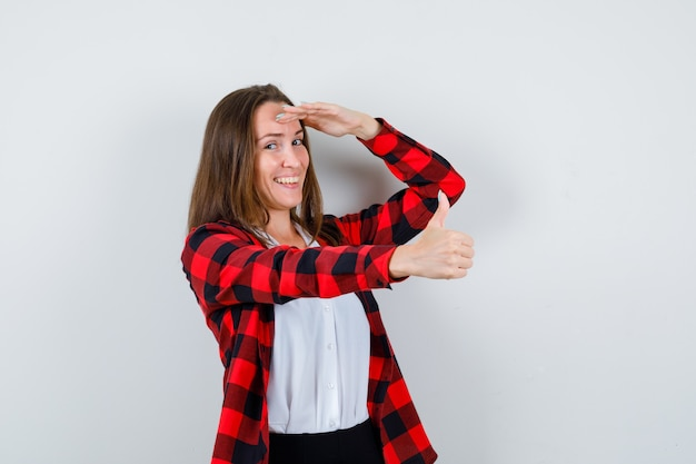 親指を立てて、カジュアルな服装で頭を抱えて陽気に見える若い女性、正面図。