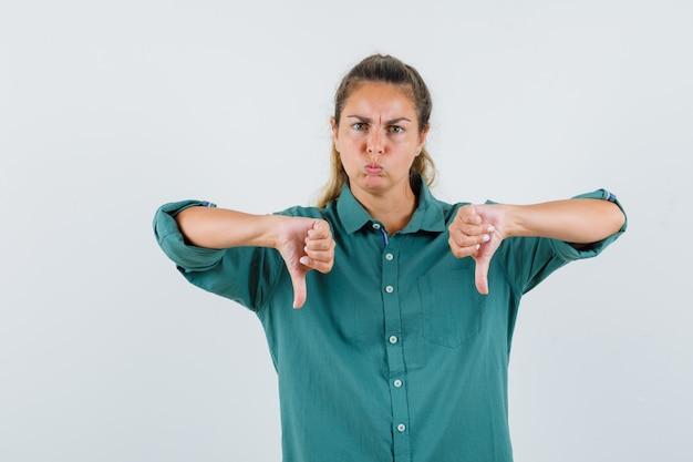 Giovane donna che mostra i pollici verso il basso e le guance gonfie in camicetta verde e sembra scontento