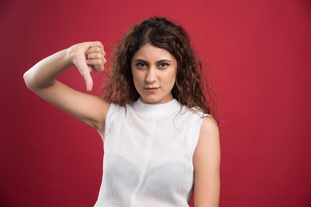 빨간색에 싫어하는 기호 아래로 엄지 손가락을 보여주는 젊은 여자.