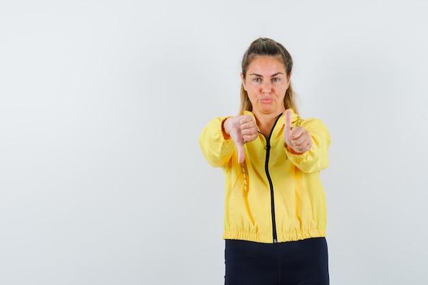 Молодая женщина показывает палец вниз обеими руками в желтой куртке-бомбардировщике и черных штанах и выглядит мило