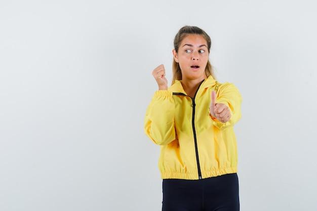 黄色のボンバージャケットと黒のズボンで左を見ながら、親指を立てて拳を握りしめ、かわいく見える若い女性