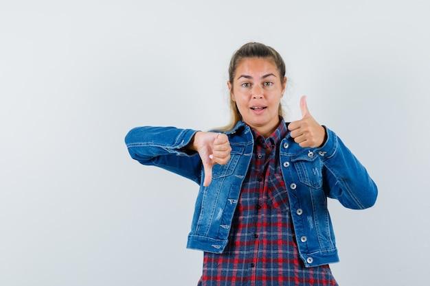 シャツ、ジャケット、陽気に見える、正面図で親指を上下に示す若い女性。