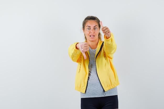 Tシャツ、ジャケットで親指を上下に示し、困惑しているように見える若い女性、正面図。