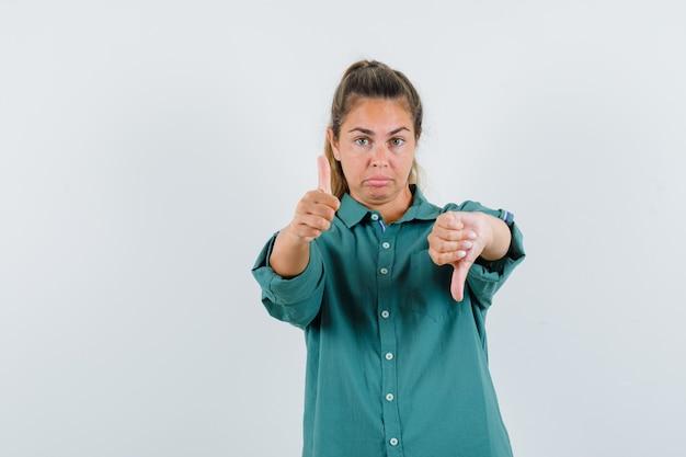 両手で親指を上下に見せ、緑のブラウスに顔をゆがめ、かわいく見える若い女性
