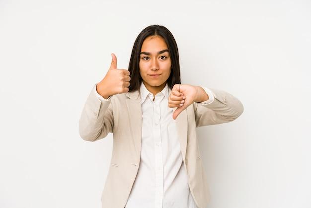 親指を上に、親指を下に示す若い女性