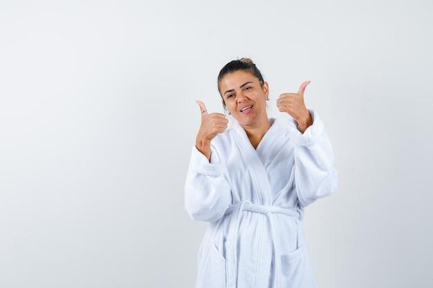 목욕 가운에 엄지손가락을 보이고 자신감을 보이는 젊은 여성