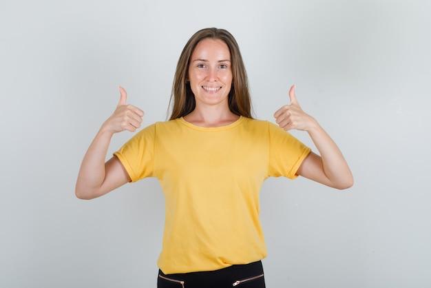 黄色のtシャツ、パンツ、陽気に見える親指を見せて若い女性