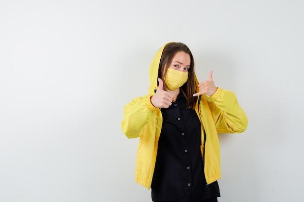 Giovane donna che mostra pollice in alto e gesto del telefono