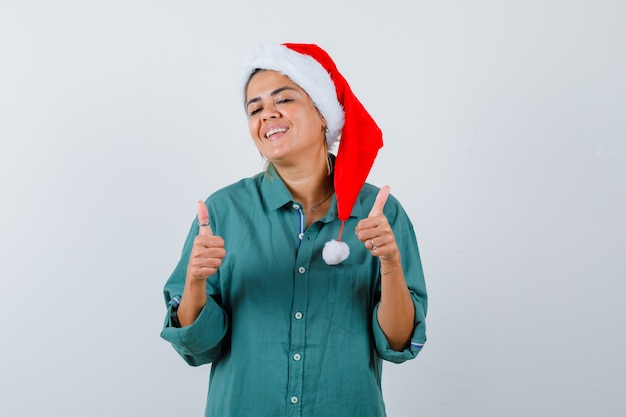 Young woman showing thumbs up in shirt, santa hat and looking satisfied , front view.