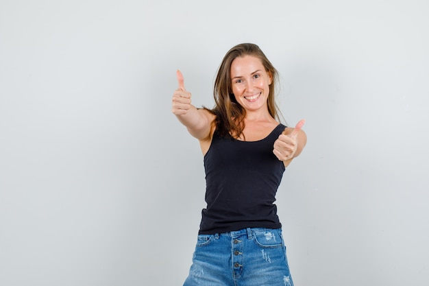 Giovane donna che mostra i pollici in su in singoletto, pantaloncini e sembra felice. vista frontale.
