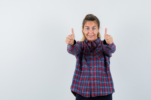 Giovane donna che mostra i pollici in su con entrambe le mani in camicia controllata e che sembra felice