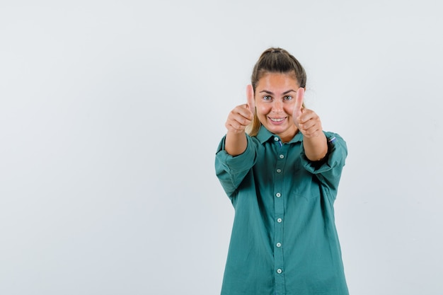 Giovane donna che mostra i pollici in su con entrambe le mani in camicetta verde e che sembra felice