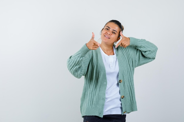 Young woman showing thumbs up with both hands in white t-shirt and mint green cardigan and looking happy