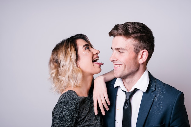 Young woman showing tongue near smiling man