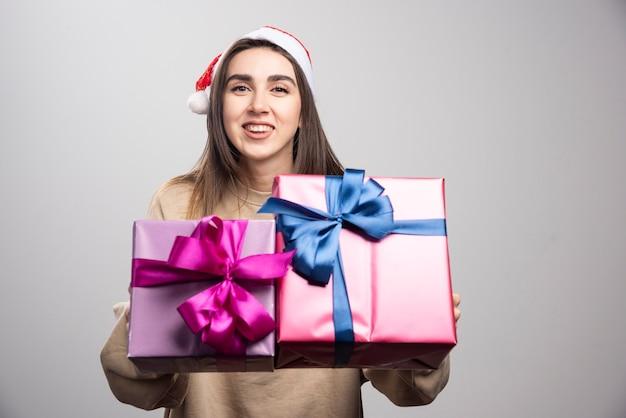 크리스마스 선물 두 상자를 보여주는 젊은 여자. 무료 사진