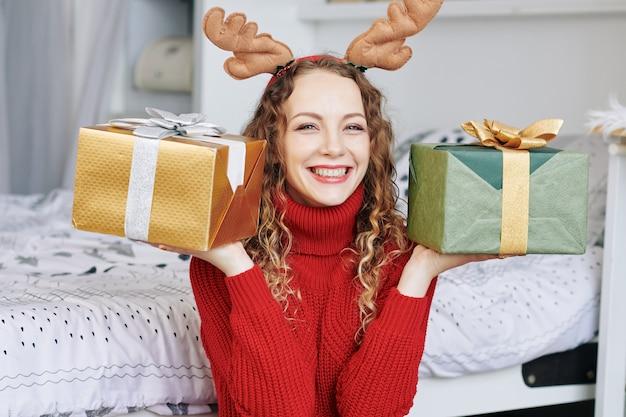 2つのプレゼントを示す若い女性