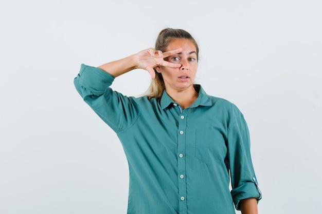 Giovane donna che mostra il segno di v sull'occhio in camicetta verde e che sembra seria