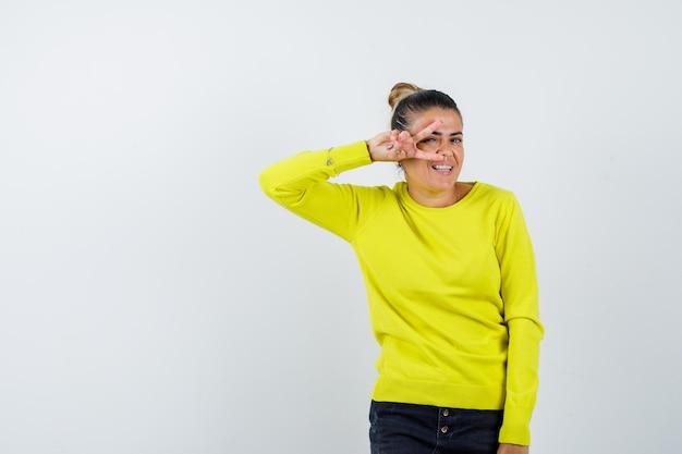 Giovane donna che mostra il segno v sull'occhio in maglione giallo e pantaloni neri e sembra felice