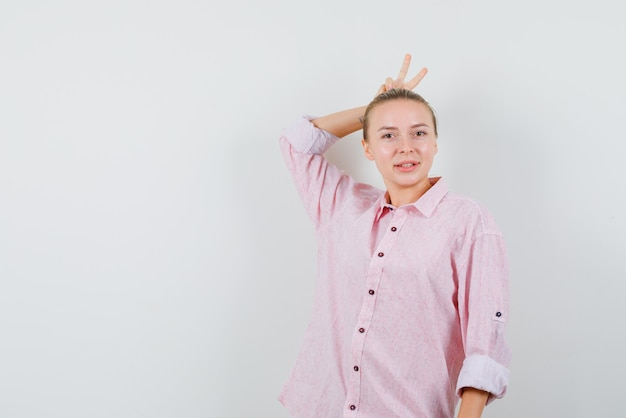Giovane donna che mostra v-segno dietro la testa come le corna in camicia rosa e sembra divertente