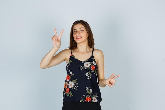 Молодая женщина показывает знак v в цветочном топе и выглядит мирно