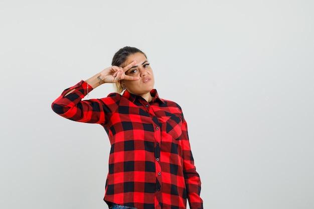 Giovane donna che mostra v-segno vicino all'occhio in camicia a quadri e sembra sicura. vista frontale.