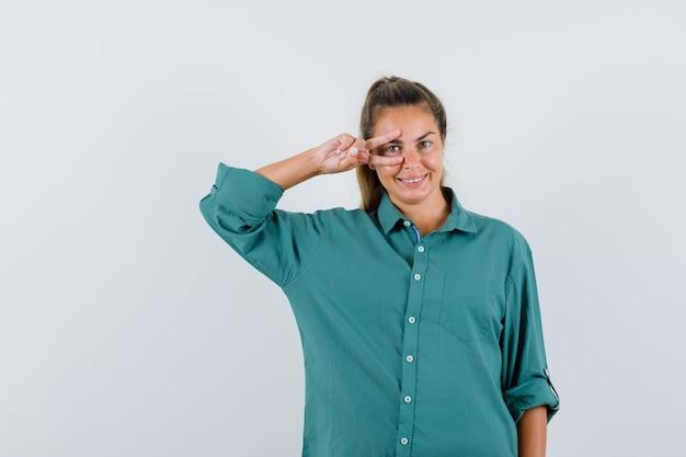 緑のブラウスとかわいく見える目のvサインを示す若い女性