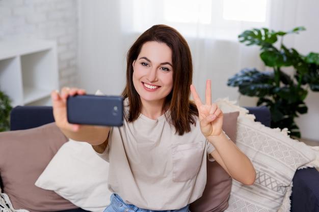 勝利のサインを示し、自宅の居心地の良いリビングルームでスマートフォンで自分撮り写真を撮る若い女性