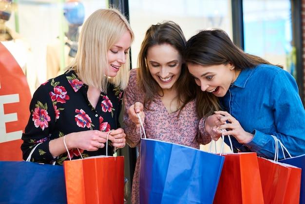 彼女が買ったものを示す若い女性