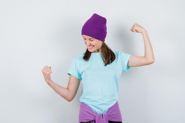 青いtシャツ、紫色のビーニーで勝者のジェスチャーを示し、幸運な顔をしている若い女性、正面図。