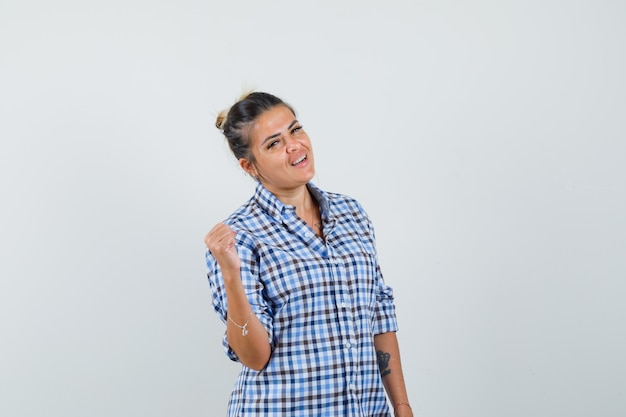 체크 무늬 셔츠에 우승자 제스처를 보여주는 젊은 여자와 행복을 찾고.
