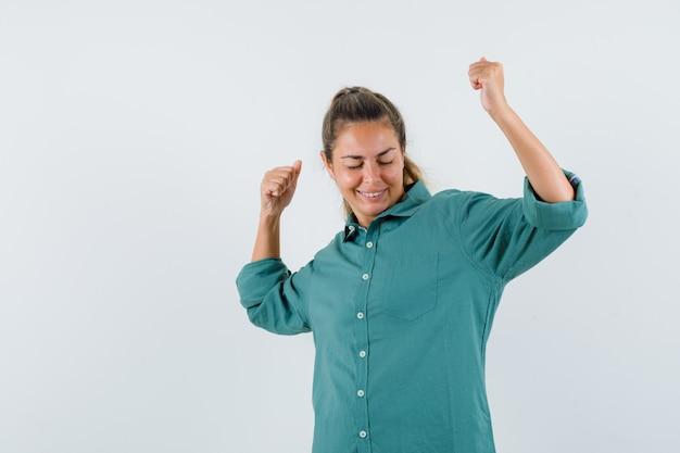 緑のブラウスで勝者のジェスチャーを示し、かわいく見える若い女性