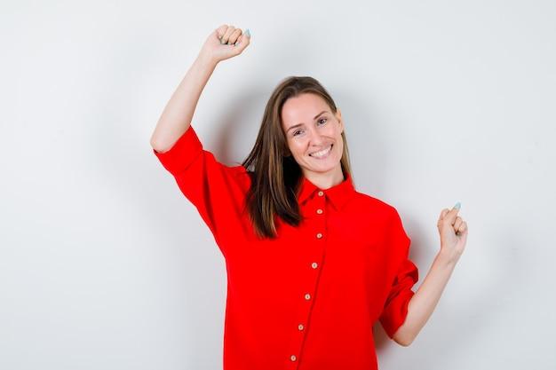 Молодая женщина показывает жест победителя в красной блузке и выглядит счастливой. передний план.