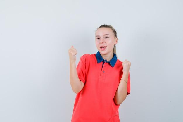 T- 셔츠에 우승자 제스처를 보여주는 행복을 찾는 젊은 여자