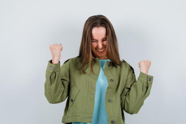 Tシャツ、ジャケット、幸運な、正面図で勝者のジェスチャーを示す若い女性。