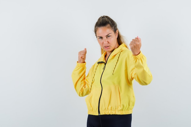 Young woman showing winner gesture in yellow bomber jacket and black pants and looking confident