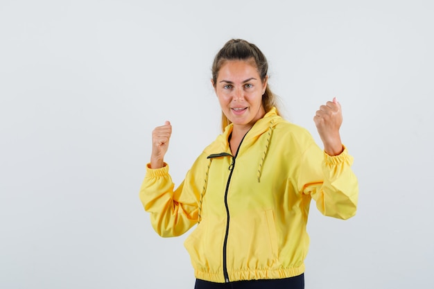 Young woman showing winner gesture in yellow raincoat and looking jolly