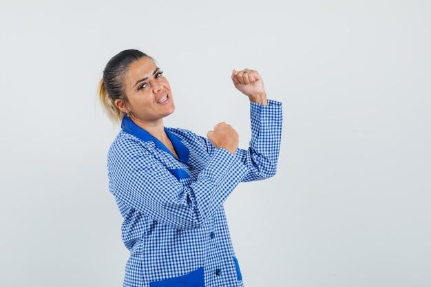 Молодая женщина показывает позу победителя в синей пижамной рубашке в клетку и выглядит красиво, вид спереди.