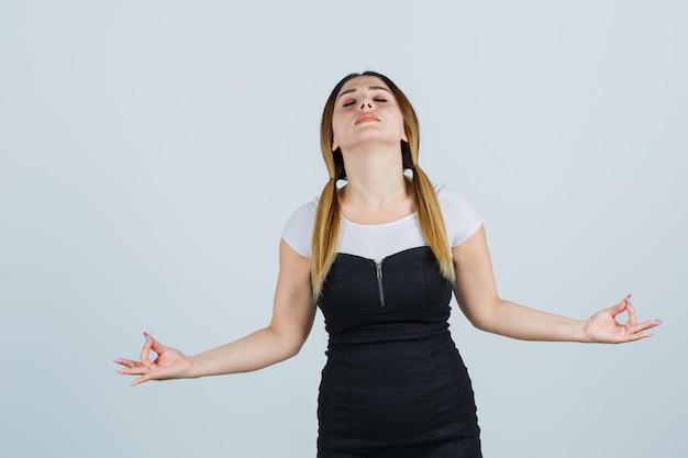 Giovane donna che mostra gesto di yoga