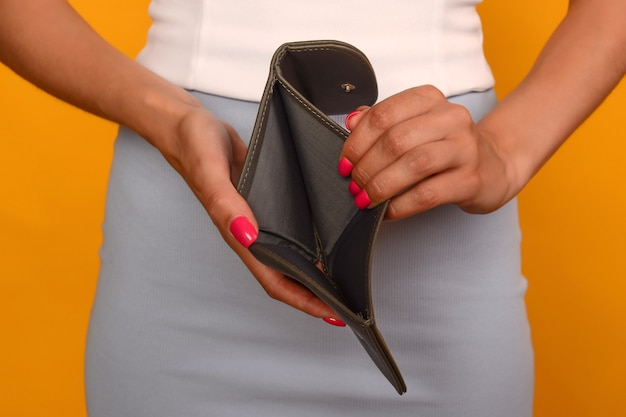 Молодая женщина показывает свой пустой бумажник. банкротство