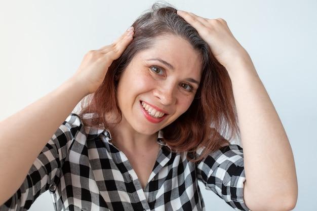 젊은 여자는 그녀의 회색 머리카락 뿌리를 보여줍니다. 조기 노화 개념.